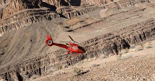 canyon red R/C helicopter flying over gray sand mountain