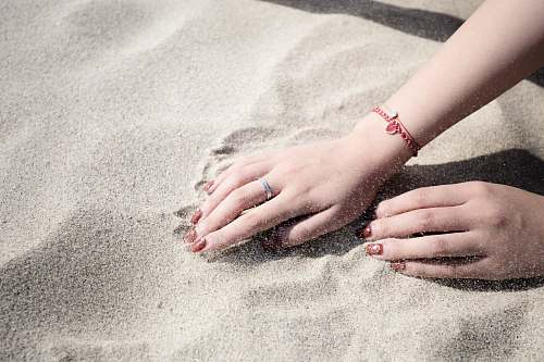 sand woman lying on white sand hands
