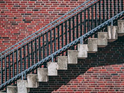 grey gray metal stair beside red brick wall abstract