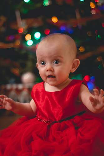 person child in red satin dress by Christmas tree baby