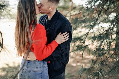 people couple kissing beside green leaf trees during daytime person
