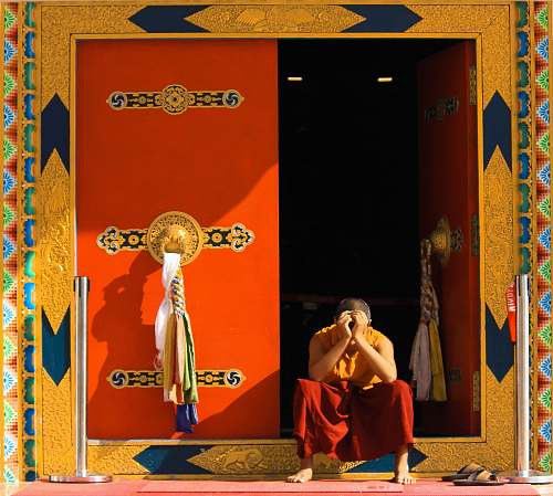 person man in orange top sitting beside door monk
