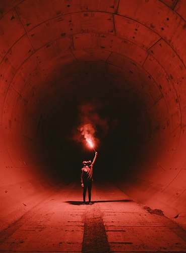 person man wearing gas mask holding torch inside tunnel tunnel