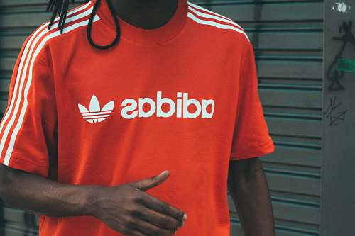 person man wearing red and white adidas crew-neck T-shirt people