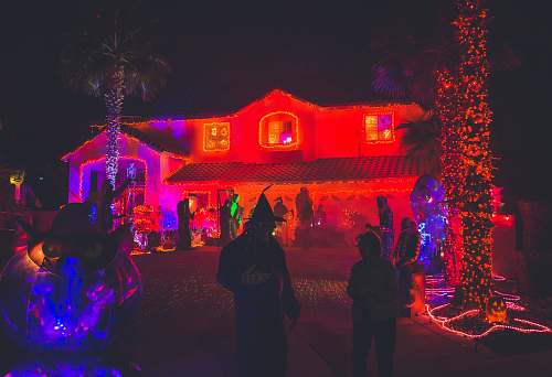 person people standing near house with red light decor during night time people