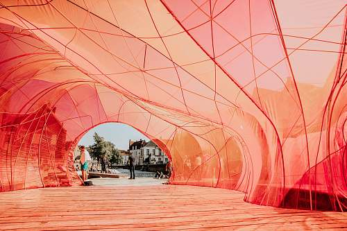 person people walking underneath red cloth path