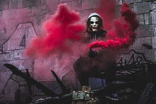 smoke person in Joker cosplay holding smoke grenade clown