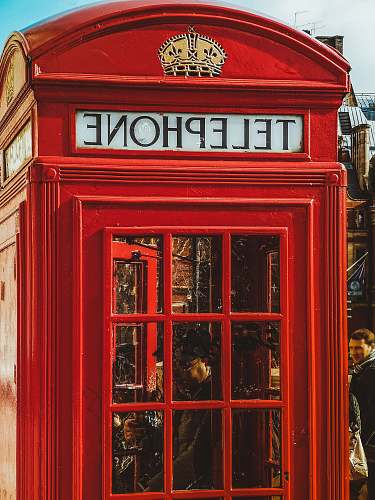 person person inside red telephone booth during daytime phone booth
