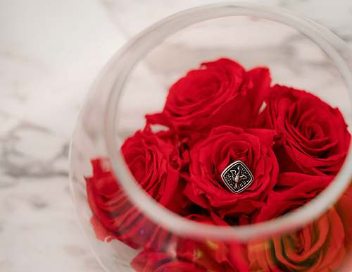 person red flowers in clear glass bowl people