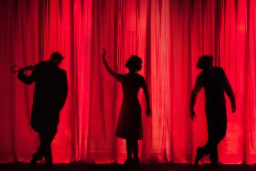 person silhouette of three performers on stage stage