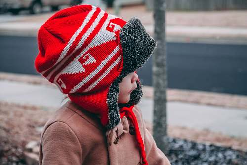people toddler wearing red and white knit hat near road during daytime hat