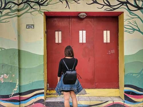 person woman facing wooden door people