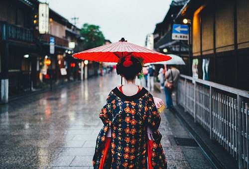 japan woman holding oil umbrella near on buildings people