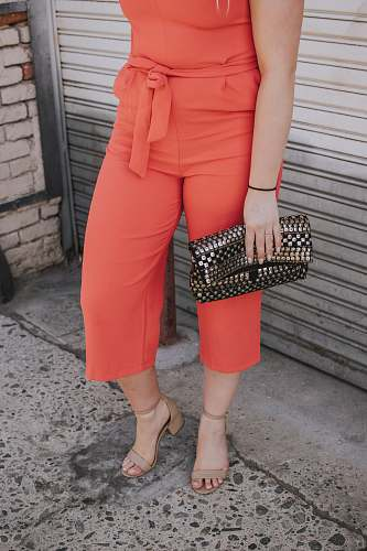 person woman in orange jumpsuit holding clutch bag people