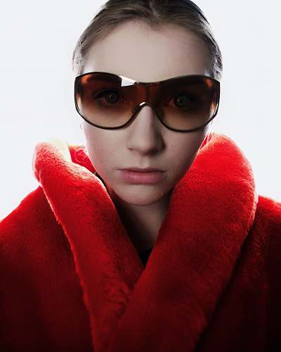 people woman in red coat wearing brown sunglasses person
