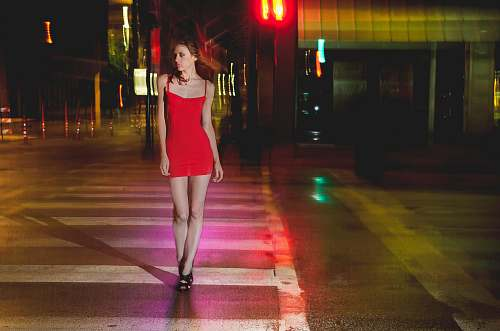 person woman in red spaghetti strap midi dress walking on pedestrian lane during nighttime city