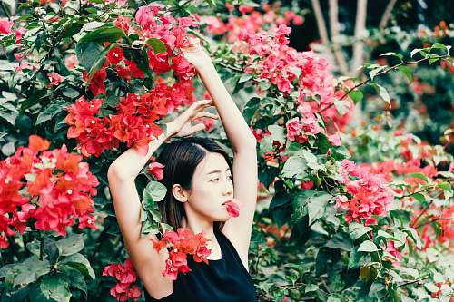 person woman standing in front of red flowers plant