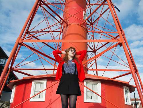 person woman standing under red metal tower people