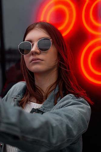 person woman wearing silver-colored framed sunglasses and blue denim collared jacket people