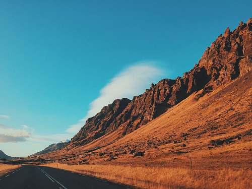 desert concrete road beside mountain under blue sky mountain