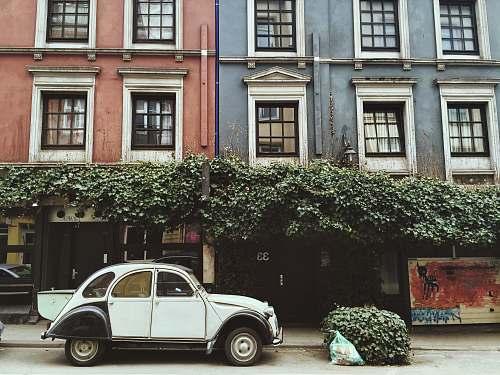car white car parked beside brown building urban