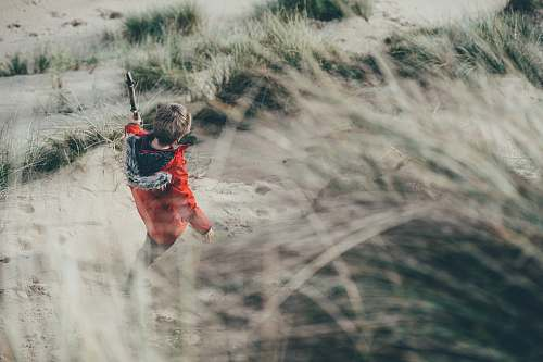 boy selective focus photo of person walking on gray sand with green grasses child
