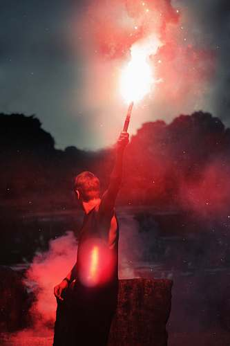 human shallow focus photo of person holding flare flare