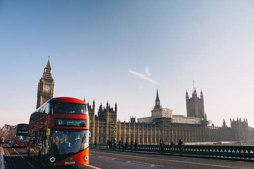 bus red double-decker bus passing Palace of Westminster, London during daytime double decker bus