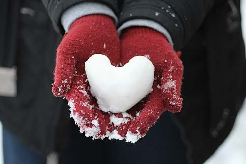 hand person holding heart-shaped snow holding