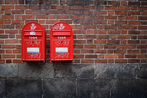 postbox photo of two red post boxes mounted in brown concrete wall denmark