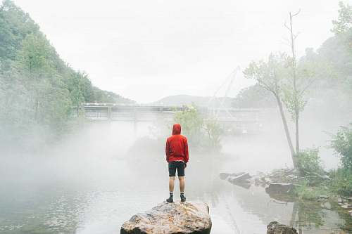 standing man standing on rock facing foggy creek lake