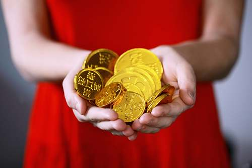 gold person holding gold-colored ching coins coin