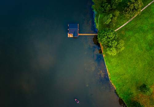 trees bird's eye view of blue wooden house on body of water near trees aerial