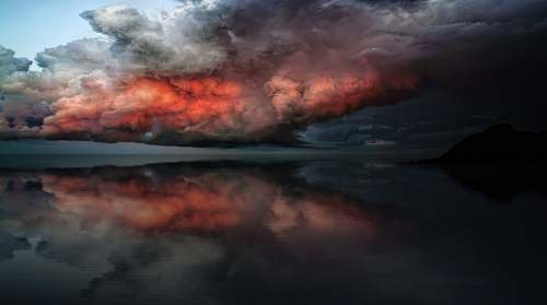sky body of water under red and white clouds cloud