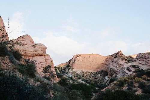 desert brown rock formation with green bushes landscape