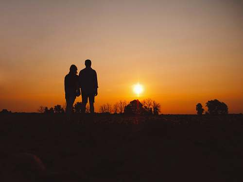 human couple stands on field during golden hour person