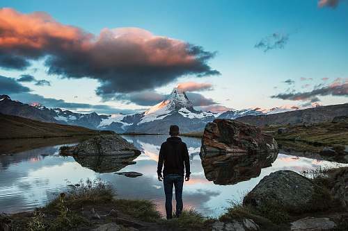 mountain man standing on rocky cliff facing body of water alps