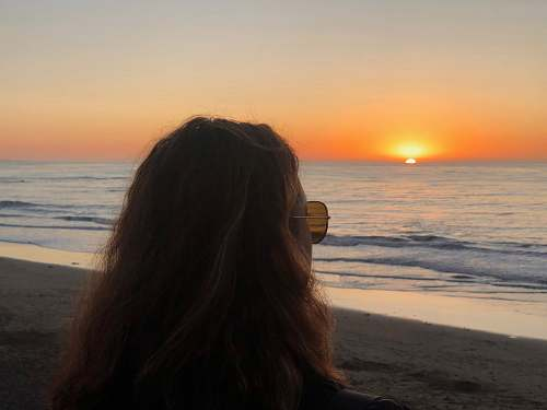 person photo of woman wearing brown sunglass looking at sunset during sunset outdoors