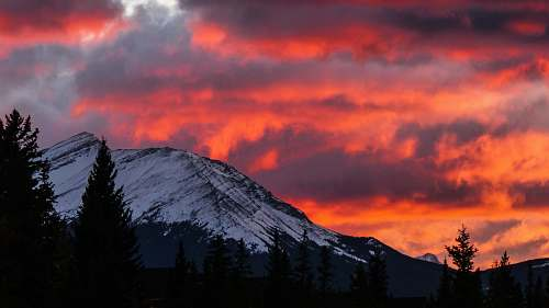sky snow covered mountain under pink clouds sky red sky