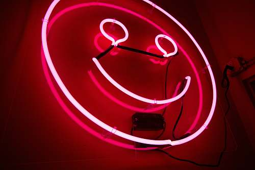red pink emoji neon signage smiley face