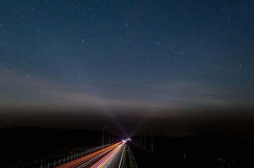 sky vehicles on road during night time stars