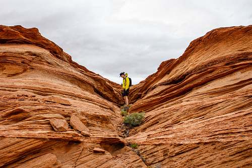 nature person in between rock formation during daytime desert
