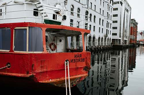 water red boat near white building boat