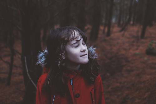 person girl wearing red coat standing near trees girl