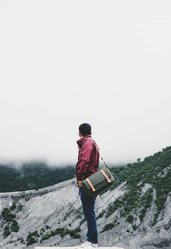 human man carrying black crossbody bag while standing on platform overlooking hill under white sky at daytime person