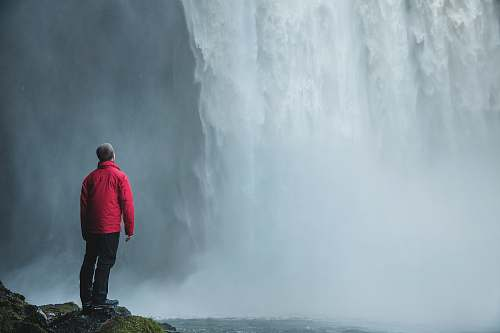 person man standing on a rock facing waterfalls human