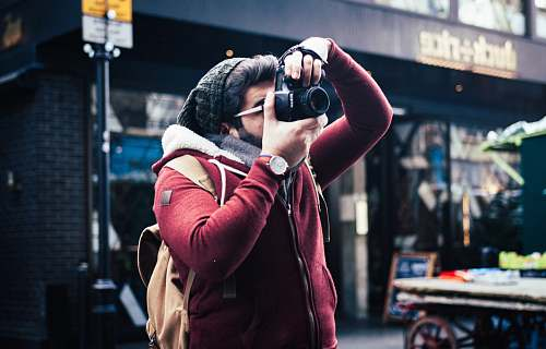 person man taking a photo near storefront human