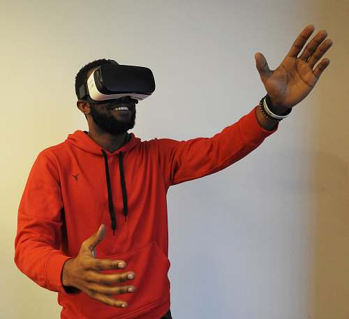 person man wearing white VR headset while lifting right hand human