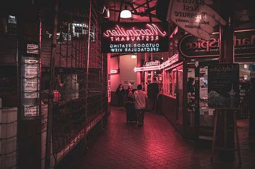 human people walking in lobby during nighttime neon
