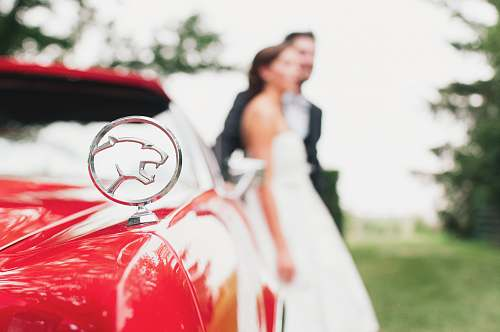 human shallow focus photography of Jaguar car emblem wedding